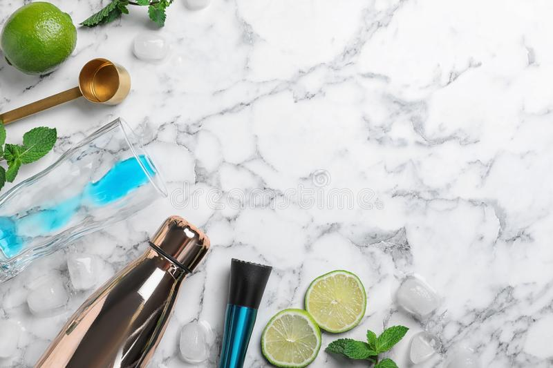 Flat lay composition with ingredients for cocktail and bar equipment on white marble background royalty free stock images