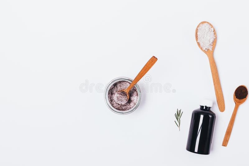 Flat lay composition jar of homemade skin scrub. Near ingredients: bottle of cosmetic oil, sea salt, ground coffee and sprig of rosemary on white background royalty free stock images