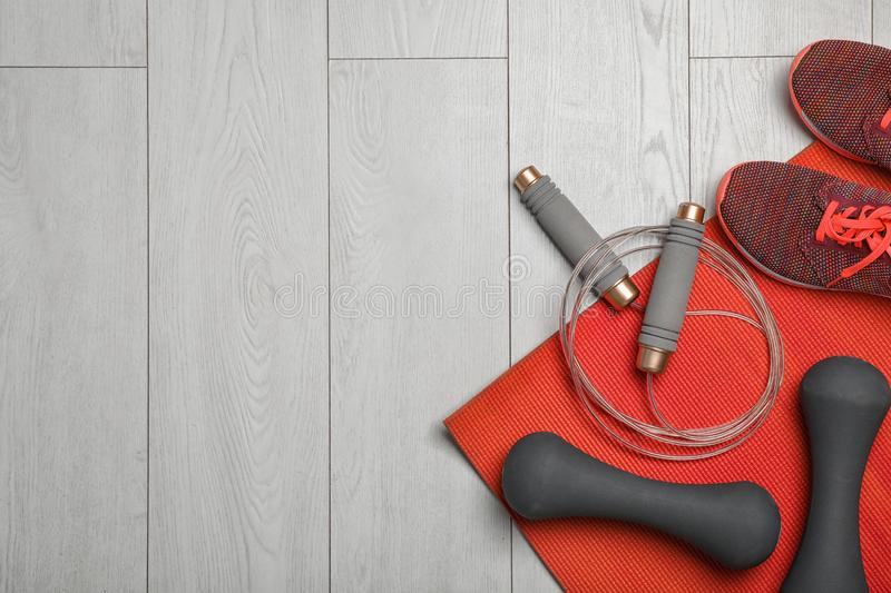 Flat lay composition with jump rope, gym equipment and space for text. On wooden background stock photography