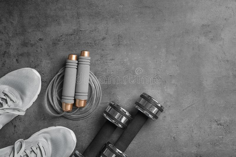 Flat lay composition with jump rope, gym equipment and space for text. On grey background stock images
