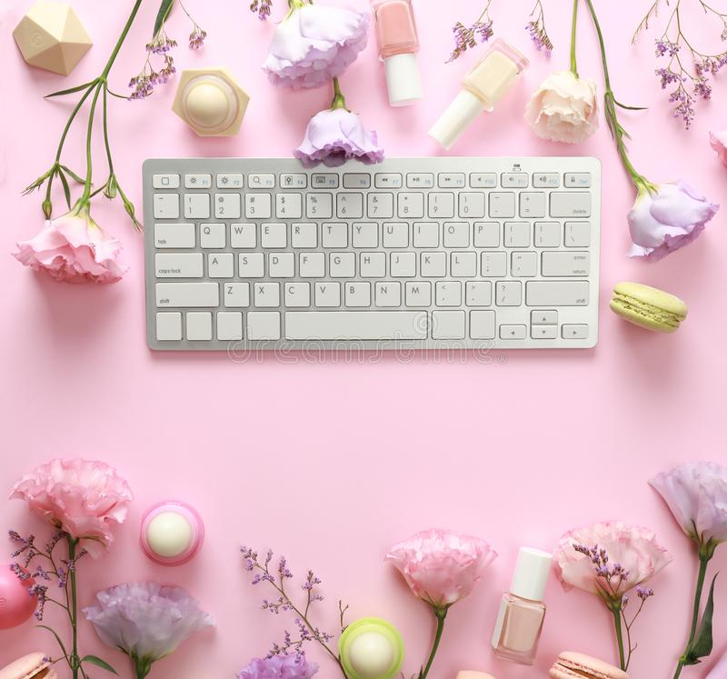 Flat lay composition with keyboard and flowers. Beauty blogger`s workplace. Flat lay composition with keyboard and flowers on pink background. Beauty blogger`s royalty free stock photography