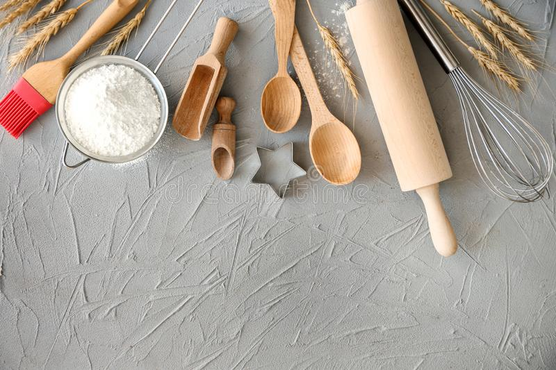 Flat lay composition with kitchen utensils and flour on grey background. Bakery workshop royalty free stock images