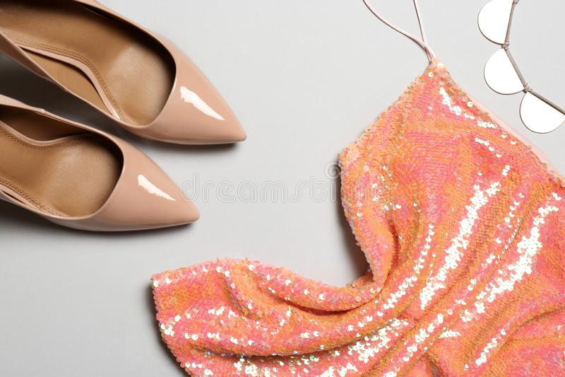 Flat lay composition with lady`s shoes and clothes. On grey background royalty free stock photography