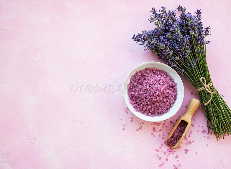 Flat lay composition with lavender flowers and natural sea salt. On pink concrete background stock photo