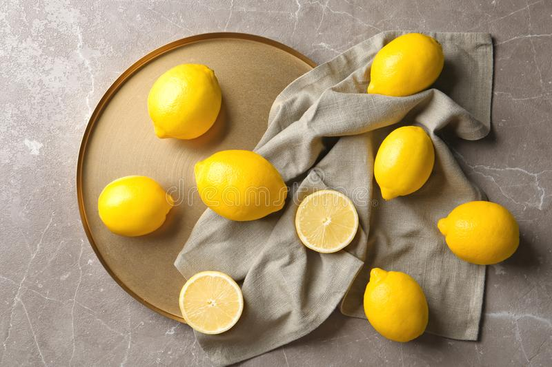 Flat lay composition with lemons, fabric and golden plate royalty free stock image