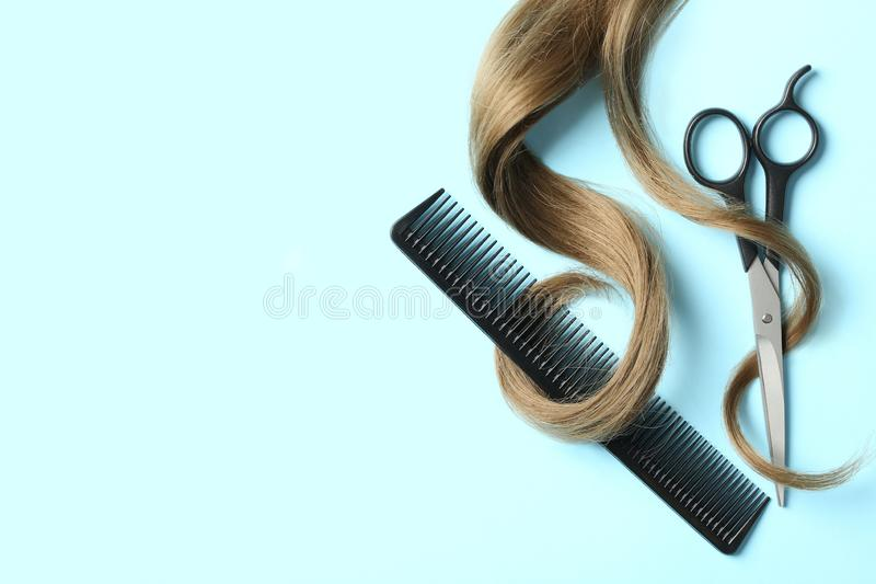 Flat lay composition with light brown hair, comb, scissors and space for text on color background. Hairdresser service stock photos