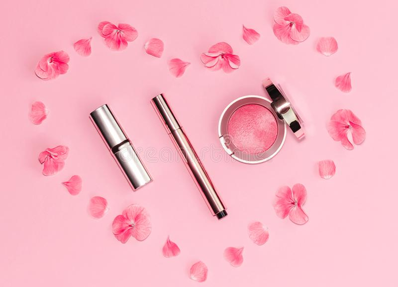Flat lay composition with makeup products and pink flowers in a shape of heart on pink background. royalty free stock images
