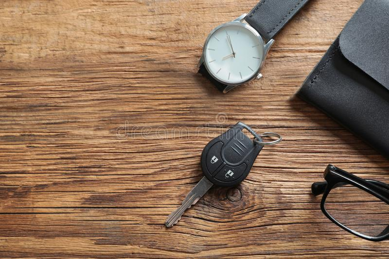 Flat lay composition with male accessories and car key on wooden background. Space for text royalty free stock photography