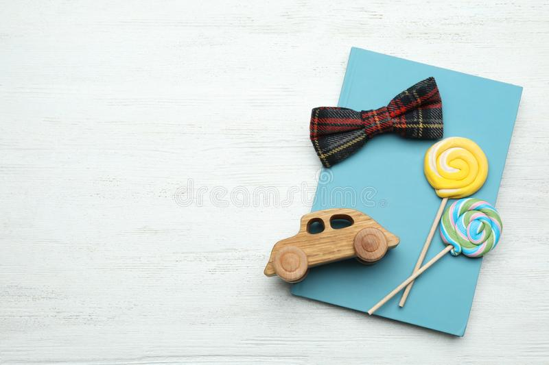 Flat lay composition with man`s accessory and candies on white wooden background. Space for text royalty free stock image