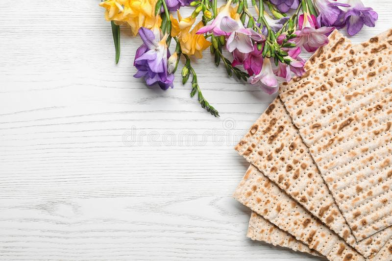 Flat lay composition of matzo and flowers on wooden background. Passover Pesach Seder. Flat lay composition of matzo and flowers on wooden background, space for stock photo