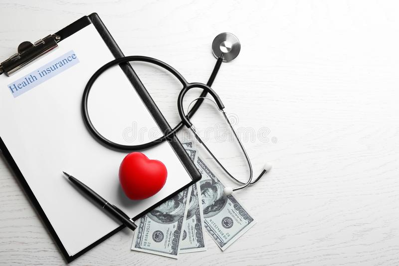 Flat lay composition with medical insurance form, money and stethoscope on white wooden table. Space for text stock photo
