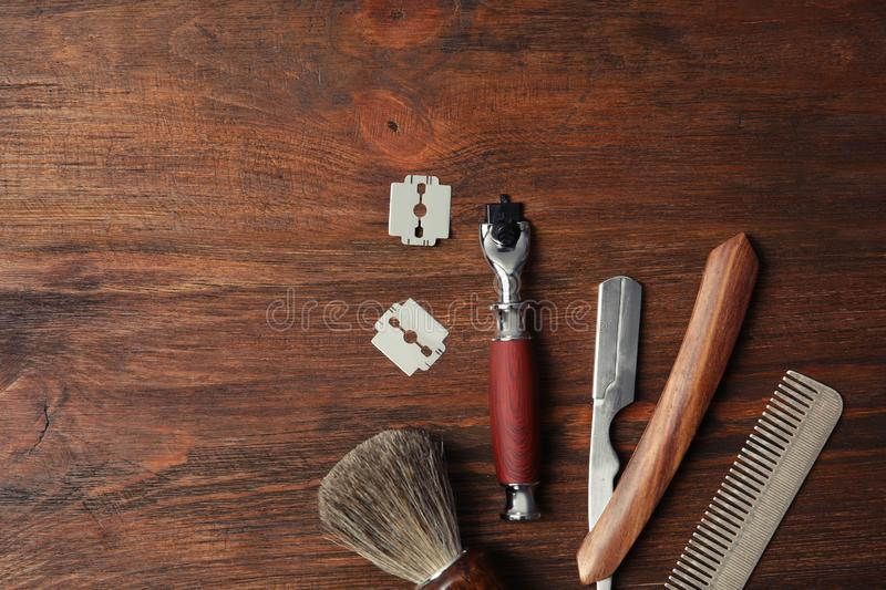 Flat lay composition with men`s shaving accessories. And space for text on wooden background royalty free stock image