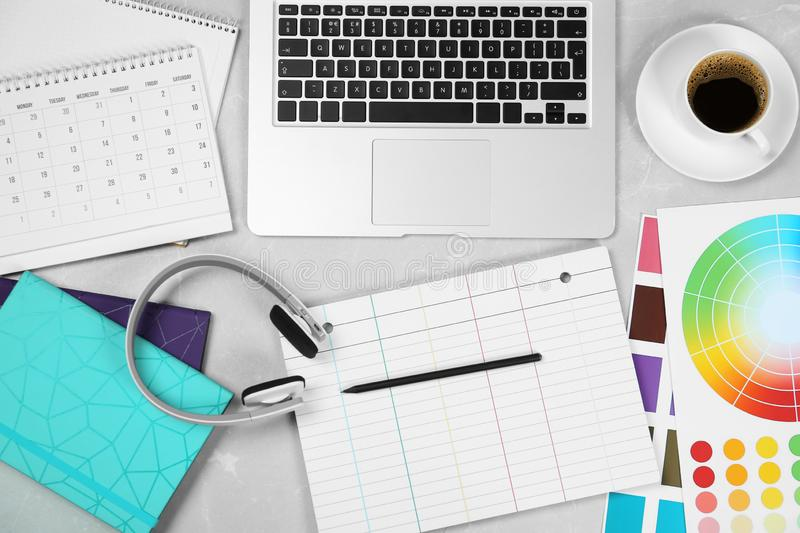 Flat lay composition with notebook, laptop and color palettes on grey marble table. Designer`s workplace. Flat lay composition with notebook, laptop and color royalty free stock images