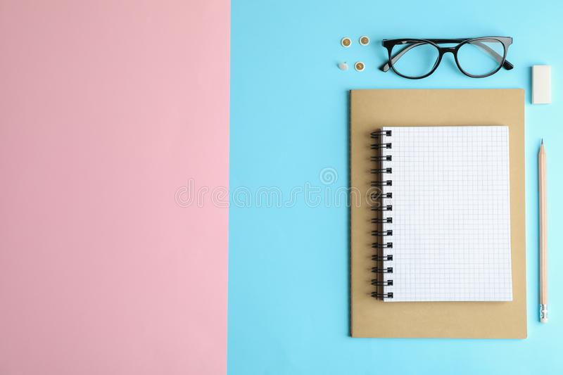 Flat lay composition with office accessories on two tone background. Space for text stock photos