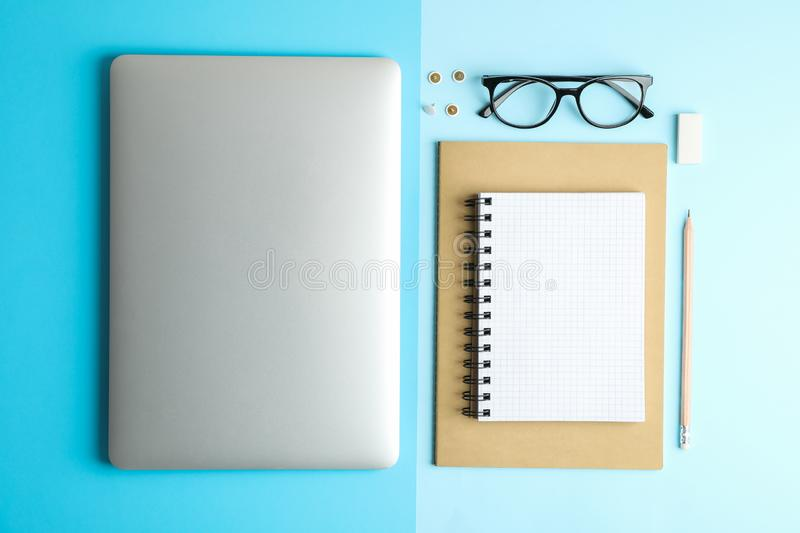 Flat lay composition with office accessories on two tone background. Space for text stock images