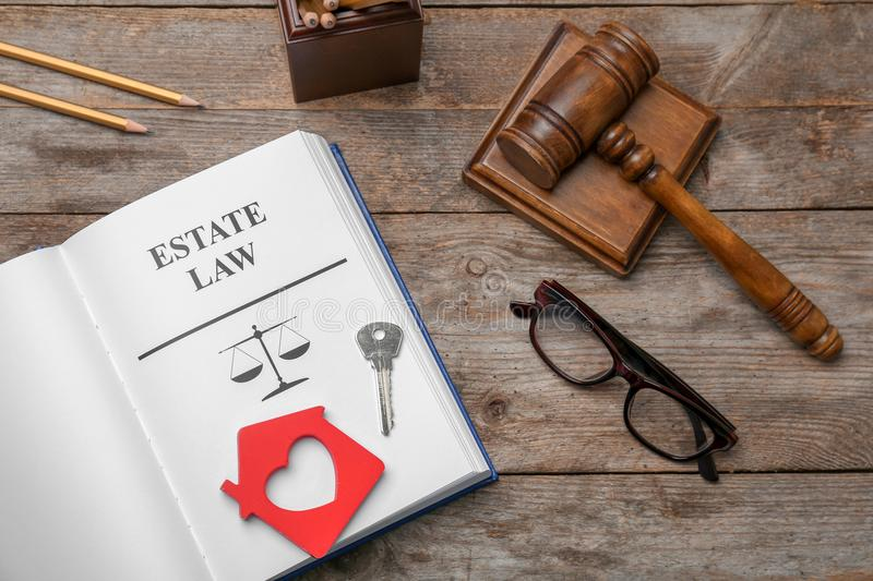 Flat lay composition with open book, gavel and house key on wooden background. Estate law concept royalty free stock photography