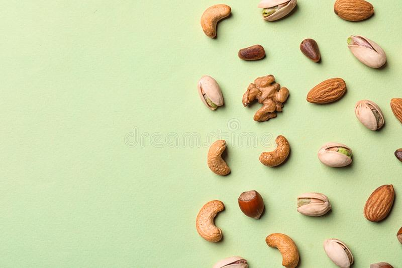 Flat lay composition with organic mixed nuts on color background. Flat lay composition with organic mixed nuts and space for text on color background stock photography