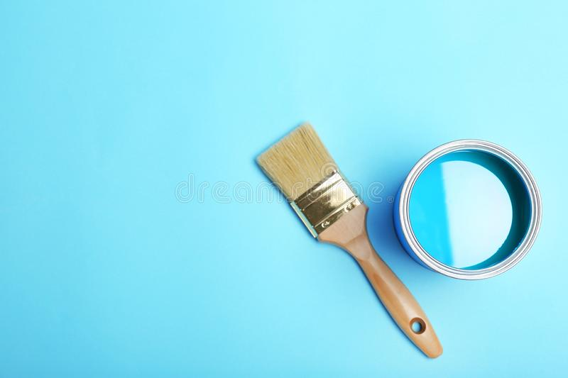 Flat lay composition with paint can and brush on color background. royalty free stock photo