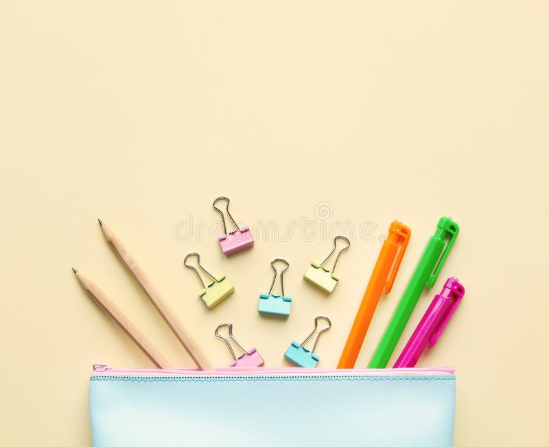Flat lay composition of pastel blue pencil case with pens, pencils,paper binders.Copy space,beige background.Top view on various stock photos