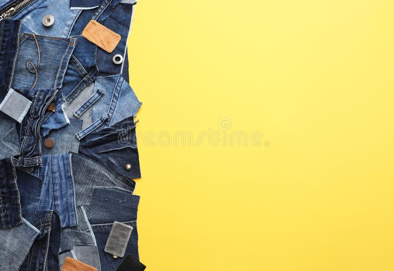 Flat lay composition with patches of old jeans on yellow. Space for text stock photo
