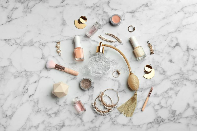 Flat lay composition with perfume bottles, jewelry and decorative cosmetics on white marble. Table royalty free stock photos