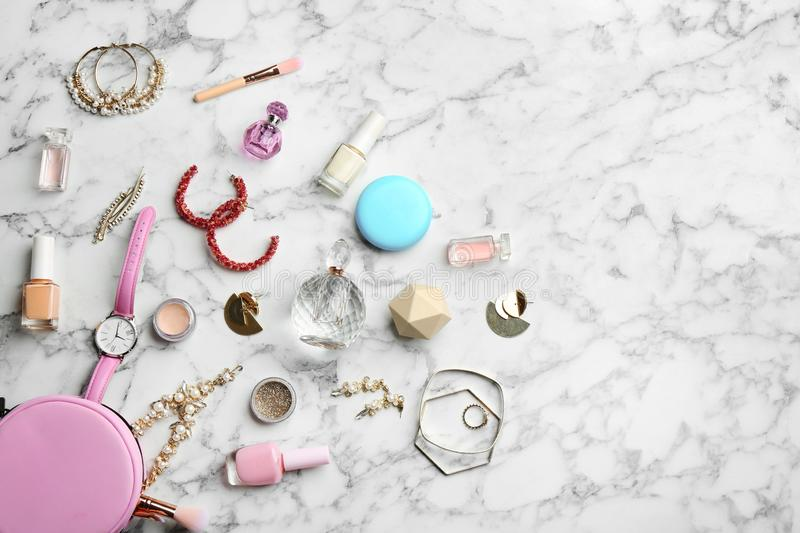 Flat lay composition with perfume bottles, jewelry and decorative cosmetics on white marble table royalty free stock photography