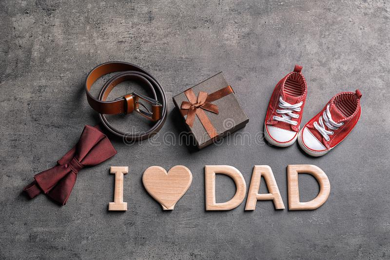 Flat lay composition with phrase I LOVE DAD small shoes and different gifts on grey background. Father`s day celebration royalty free stock photos