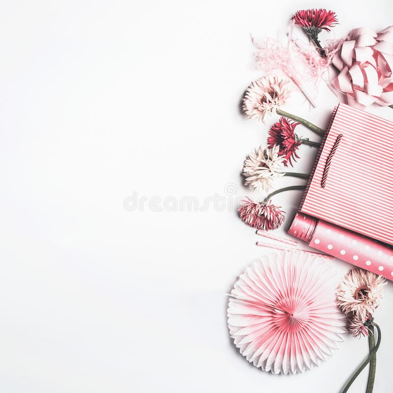 Flat lay composition of pink accessories to female holidays: Mothers day , Womens day, birthday. Paper shopping bag with flowers,. Paper, party fan and ribbon on royalty free stock photos