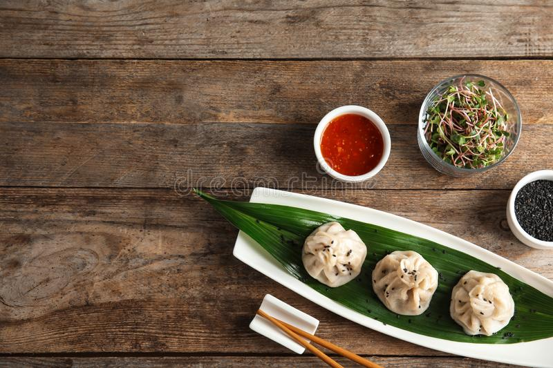Flat lay composition with plate of tasty baozi dumplings, sesame seeds, sprouts and sauce on wooden table royalty free stock photo