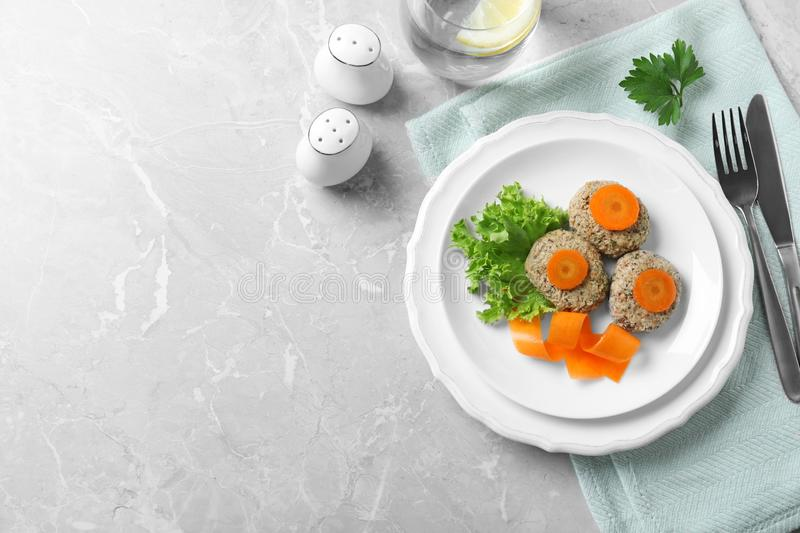 Flat lay composition with plate of traditional Passover Pesach gefilte fish on grey background. Space for text stock photos