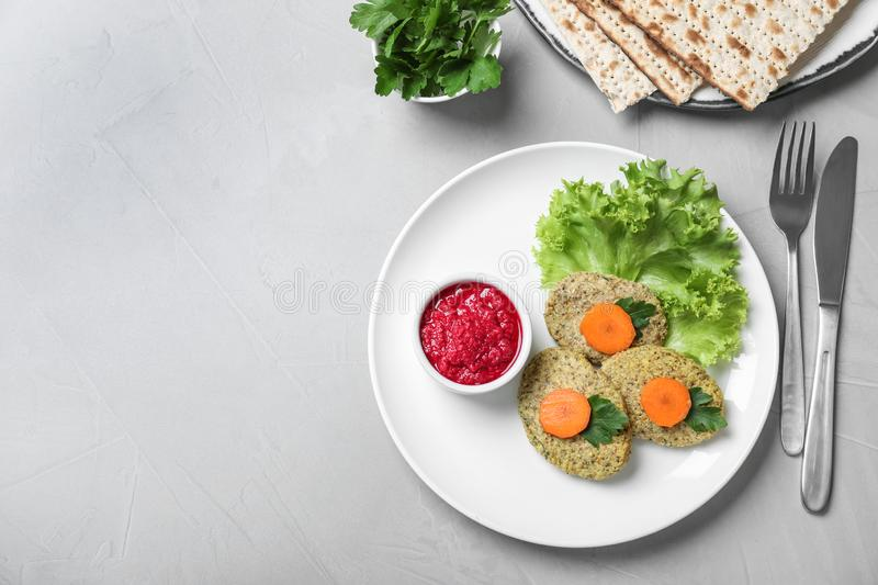 Flat lay composition with plate of traditional Passover Pesach gefilte fish on light background. Space for text stock images
