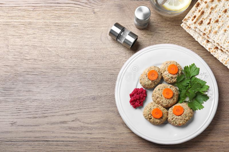 Flat lay composition with plate of traditional Passover Pesach gefilte fish on wooden background. Space for text stock image