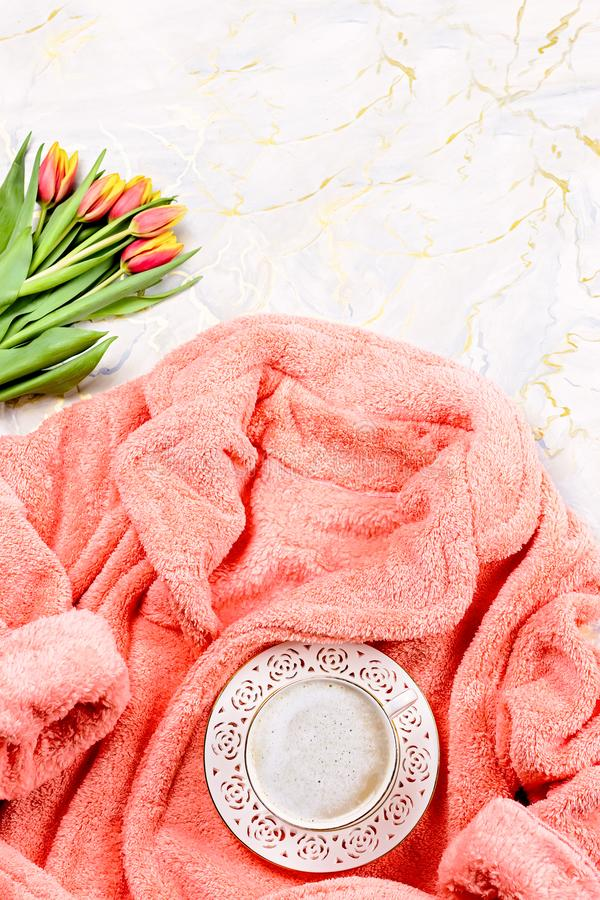 Flat lay composition with plush pink bathrobe, coffee, flowers on marble background, top view, copy space. Flat lay composition with plush pink bathrobe, coffee royalty free stock photo