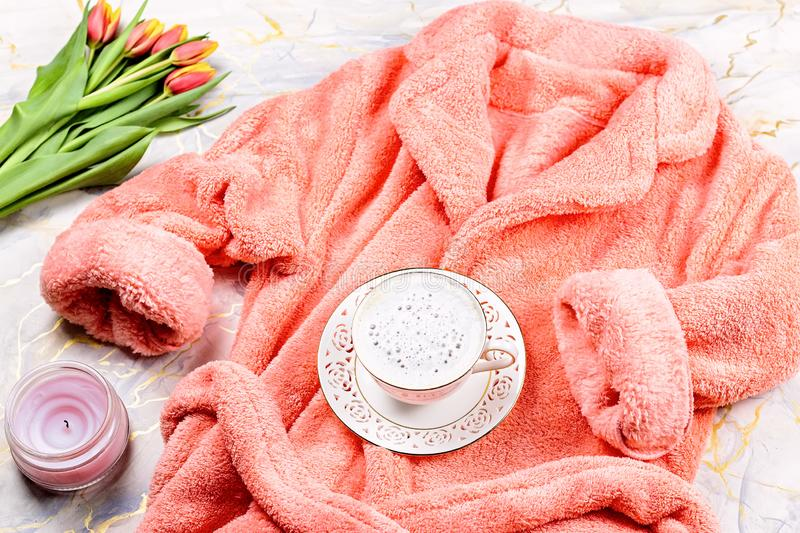Flat lay composition with plush pink bathrobe, coffee, flowers on marble background, top view, copy space. Flat lay composition with plush pink bathrobe, coffee stock images