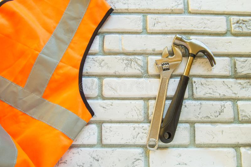 Flat lay composition with protective construction vest and working tool on brick wall background royalty free stock photos