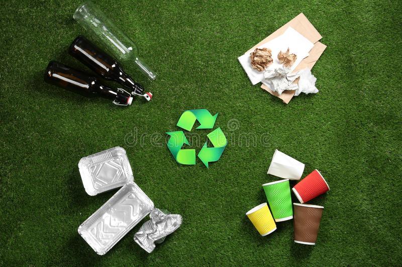 Flat lay composition with recycling symbol and different garbage. On green grass royalty free stock photo