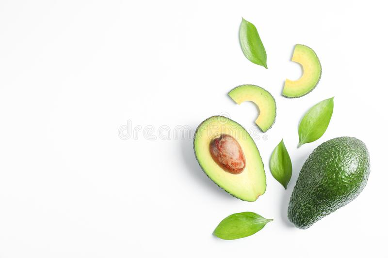 Flat lay composition with ripe avocados on white background, space for text royalty free stock image