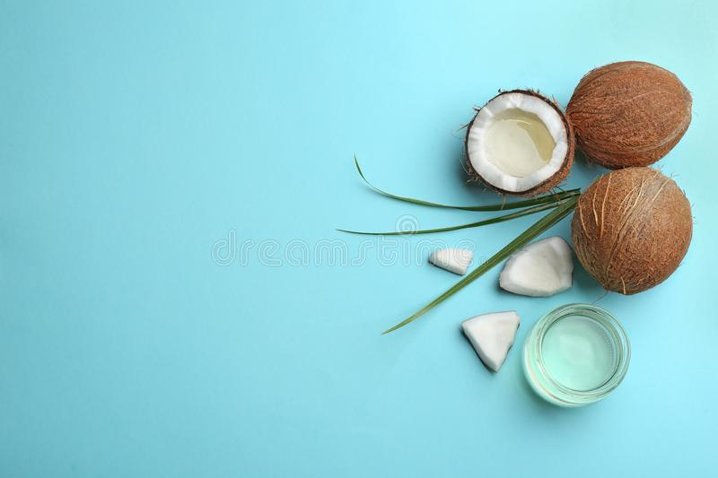 Flat lay composition with ripe coconuts, natural organic oil on blue background stock image