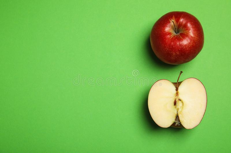 Flat lay composition with ripe juicy red apples on green background. Space for text stock photo