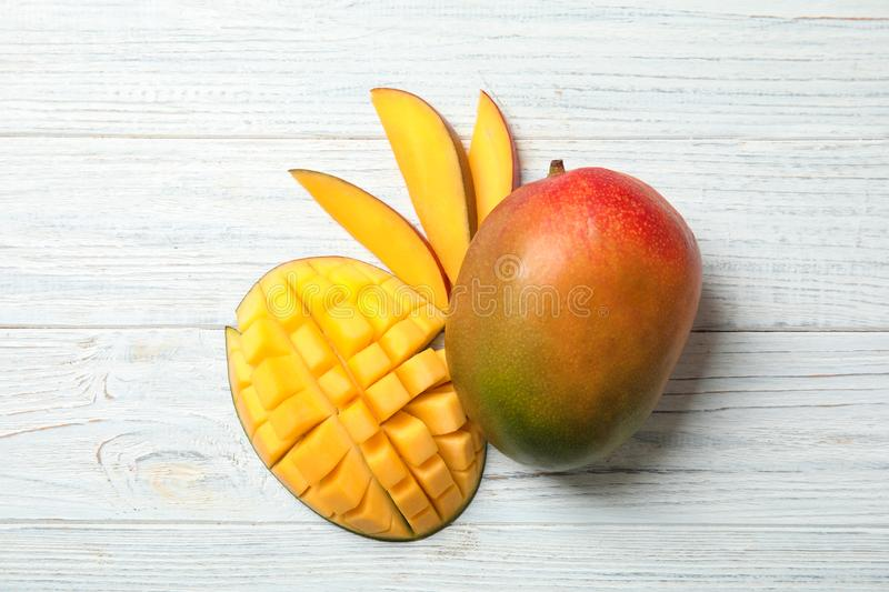 Flat lay composition with ripe mangoes on white background. Flat lay composition with ripe mangoes on white wooden background royalty free stock photography