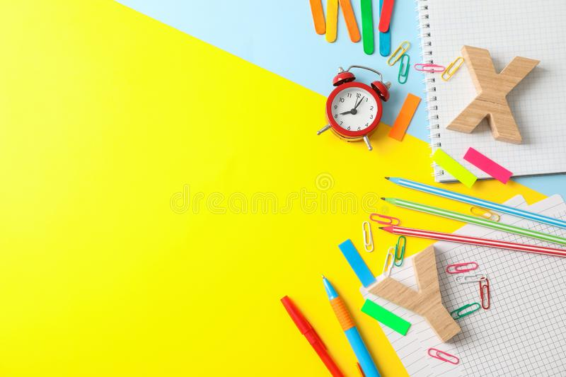 Flat lay composition with school supplies on two tone background. Space for text stock photography