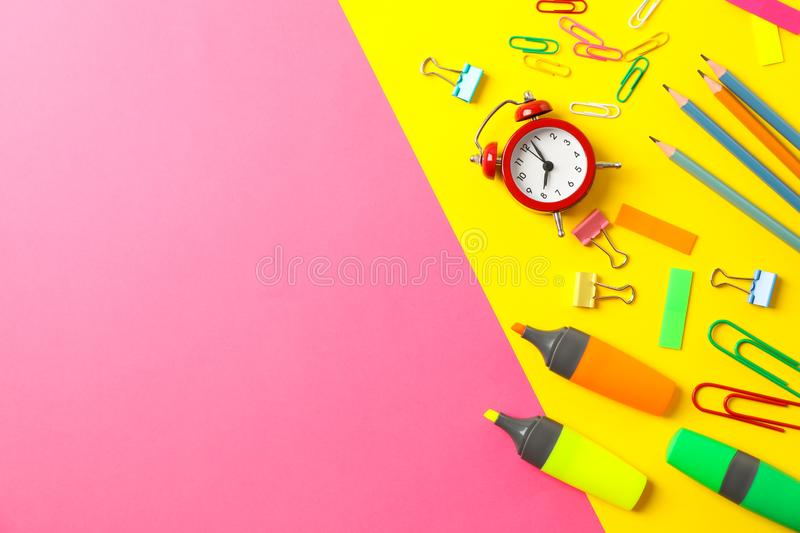 Flat lay composition with school supplies on two tone background. Space for text stock image