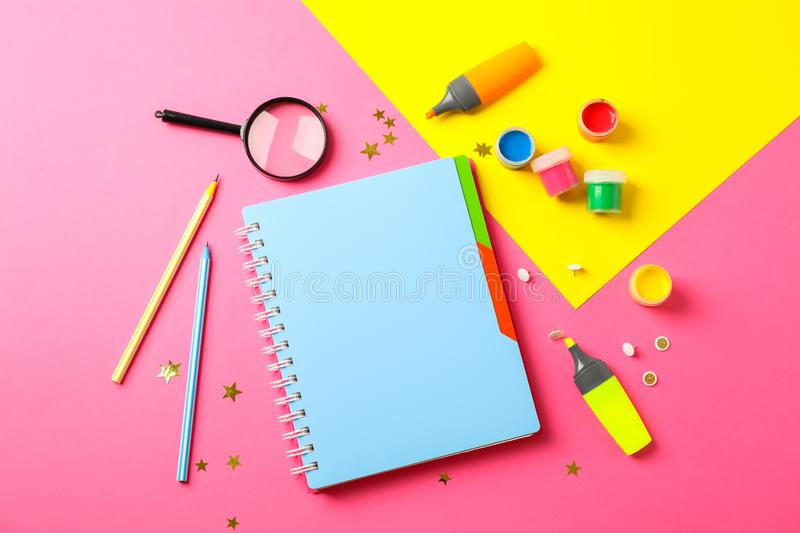 Flat lay composition with school supplies on two tone background. Space for text stock images