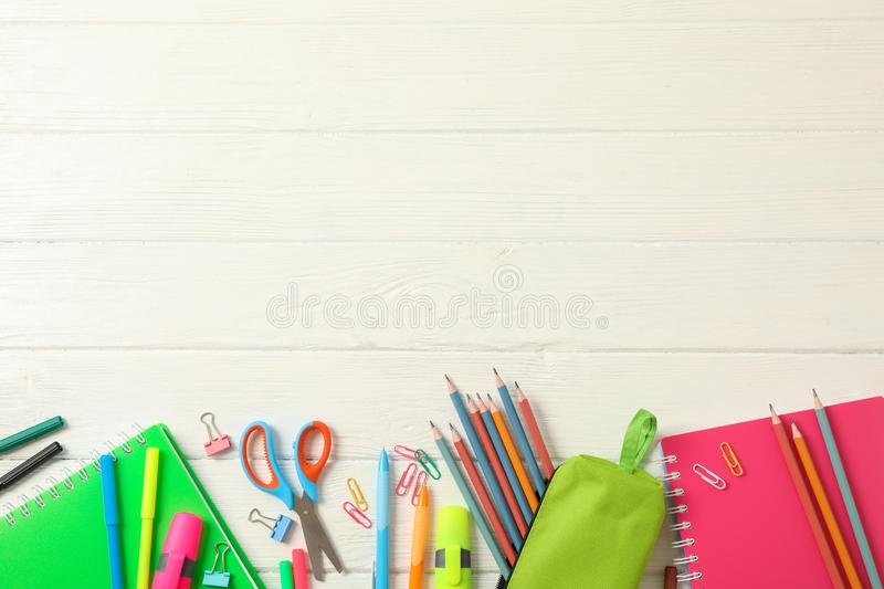 Flat lay composition with school supplies on white wooden background. Space for text royalty free stock photo