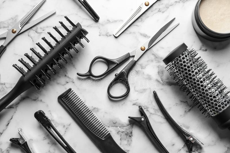 Flat lay composition with scissors and other hairdresser`s accessories on white marble. Background stock photos