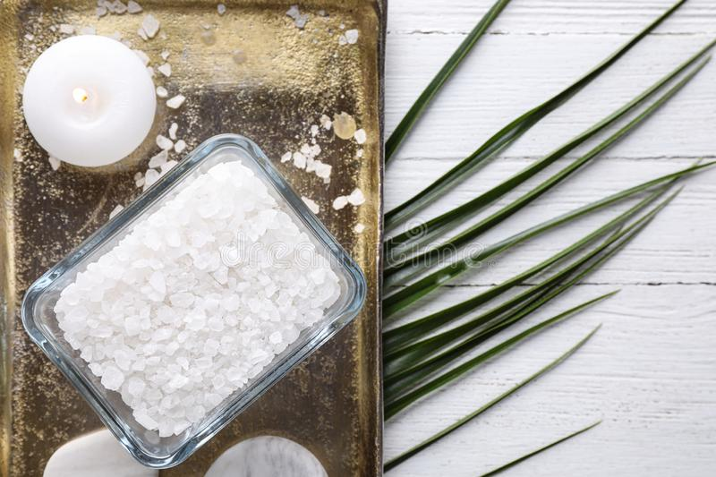 Flat lay composition with sea salt on white wooden background. Spa treatment. Flat lay composition with sea salt on white wooden background, space for text. Spa royalty free stock photo