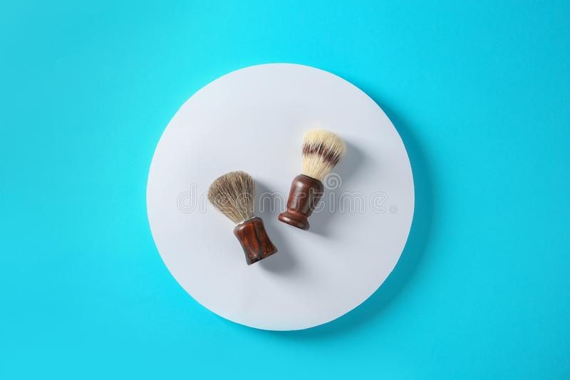 Flat lay composition with shaving brushes. On color background royalty free stock photography