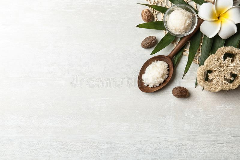 Flat lay composition with Shea butter and nuts on light background. Space for text royalty free stock image