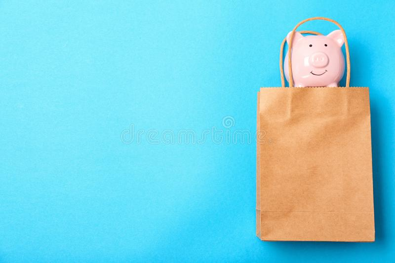 Flat lay composition with shopping bag and piggy bank. On color background royalty free stock image