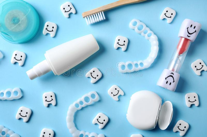 Flat lay composition with small plastic teeth and dental care items. On color background royalty free stock image